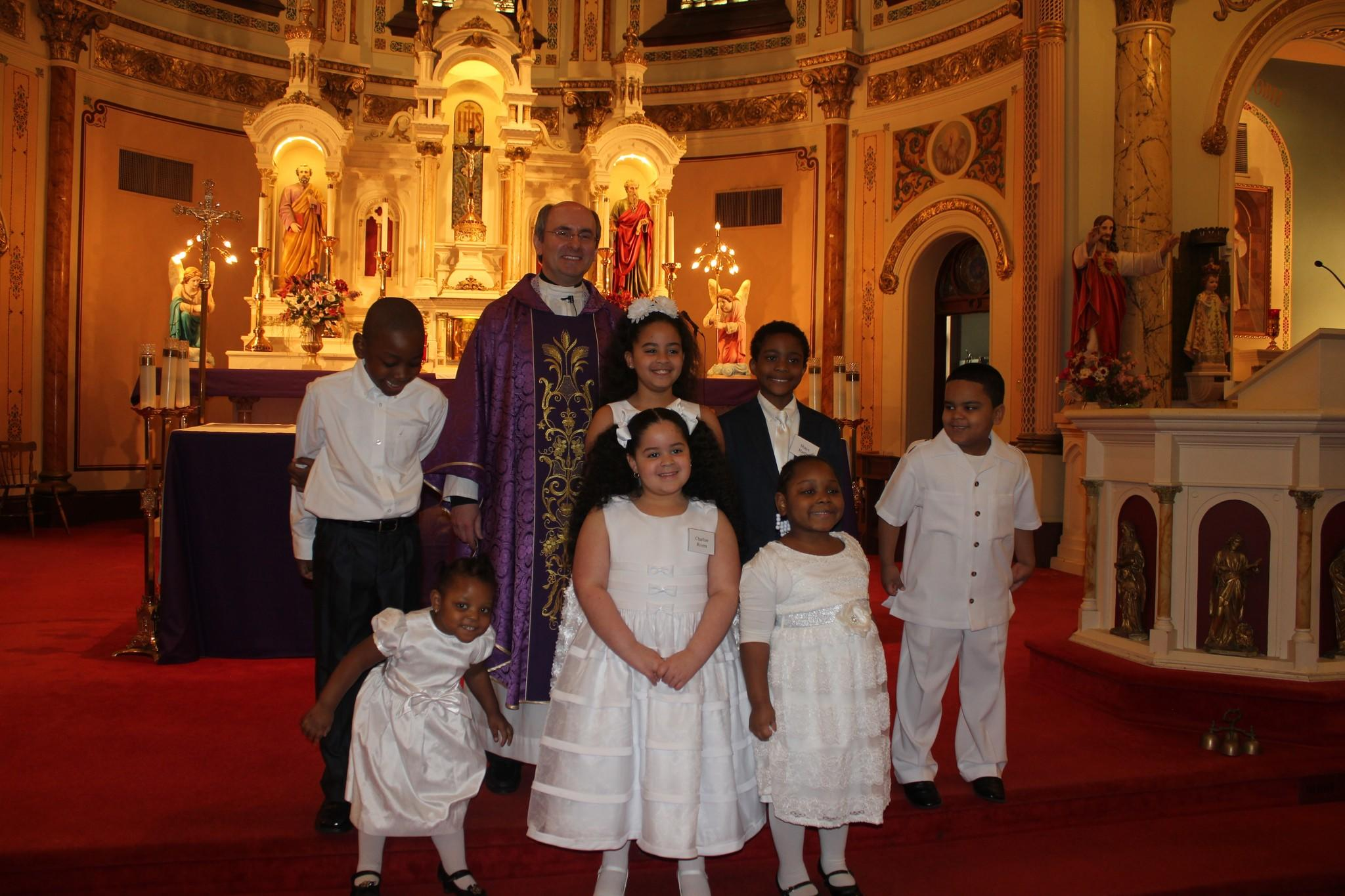 Fr. Adam Hurbanczuk with students at the Baptismal ceremony.