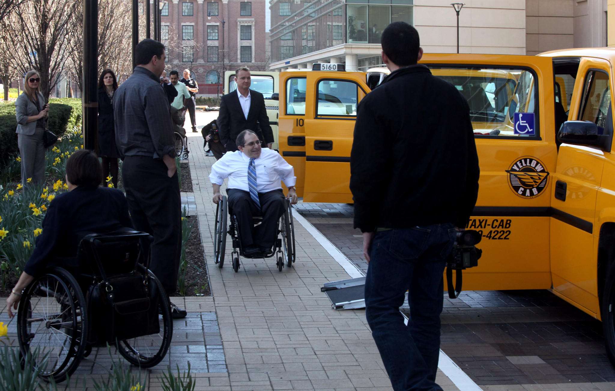 Joe Russo, center, prepares to board one of several wheelchair accessible cabs parked at McCormick Place.