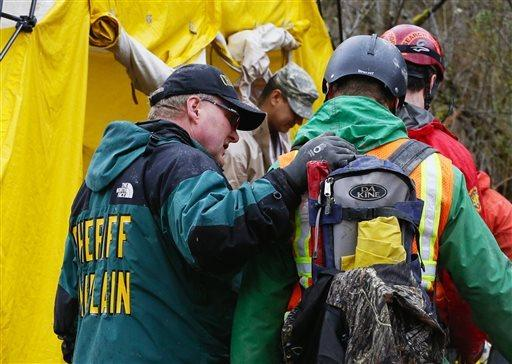 A sheriff's chaplain offers a few words to a rescue worker in Arlington, Wash., on Sunday.