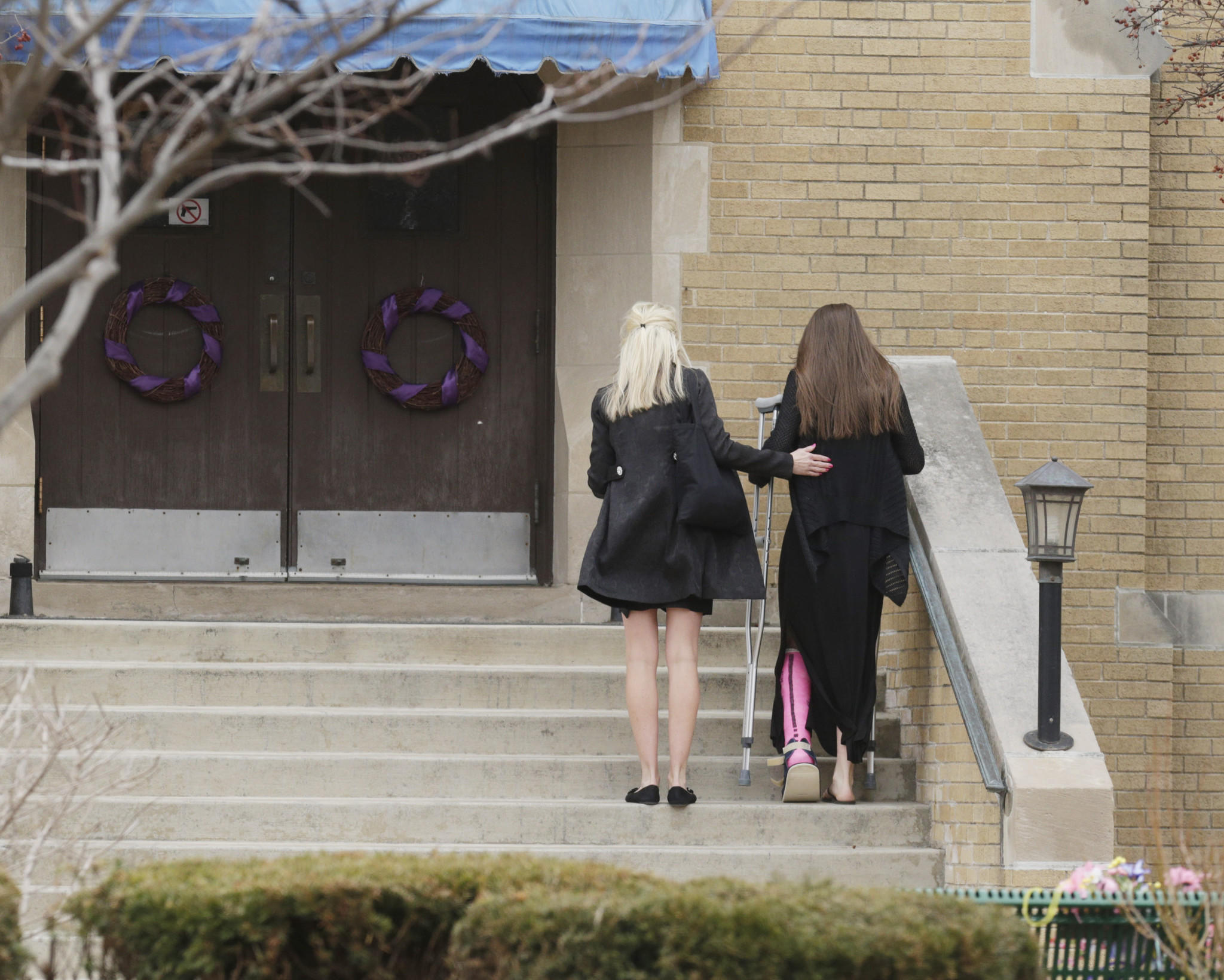 Keyana Linbo, right, the teen injured in the plane crash that killed her friend, Katherine Bronken, 15, and her father, Jeffrey Bronken, is helped up the stairs outside of St. Bede Church in Ingleside on April 1.