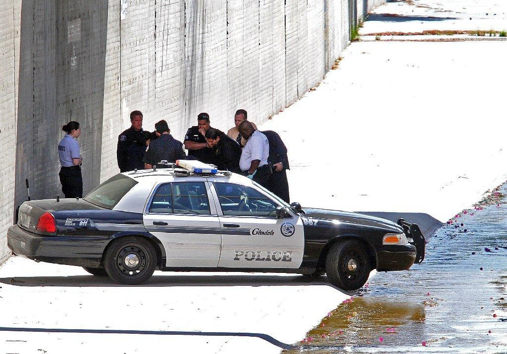 Glendale Police and Los Angeles County Coroner officials investigate the scene where a body was found near Glorietta Park inside a suitcase that was dumped in the wash that runs through the park, under the Glorietta Avenue Bridge in Glendale.