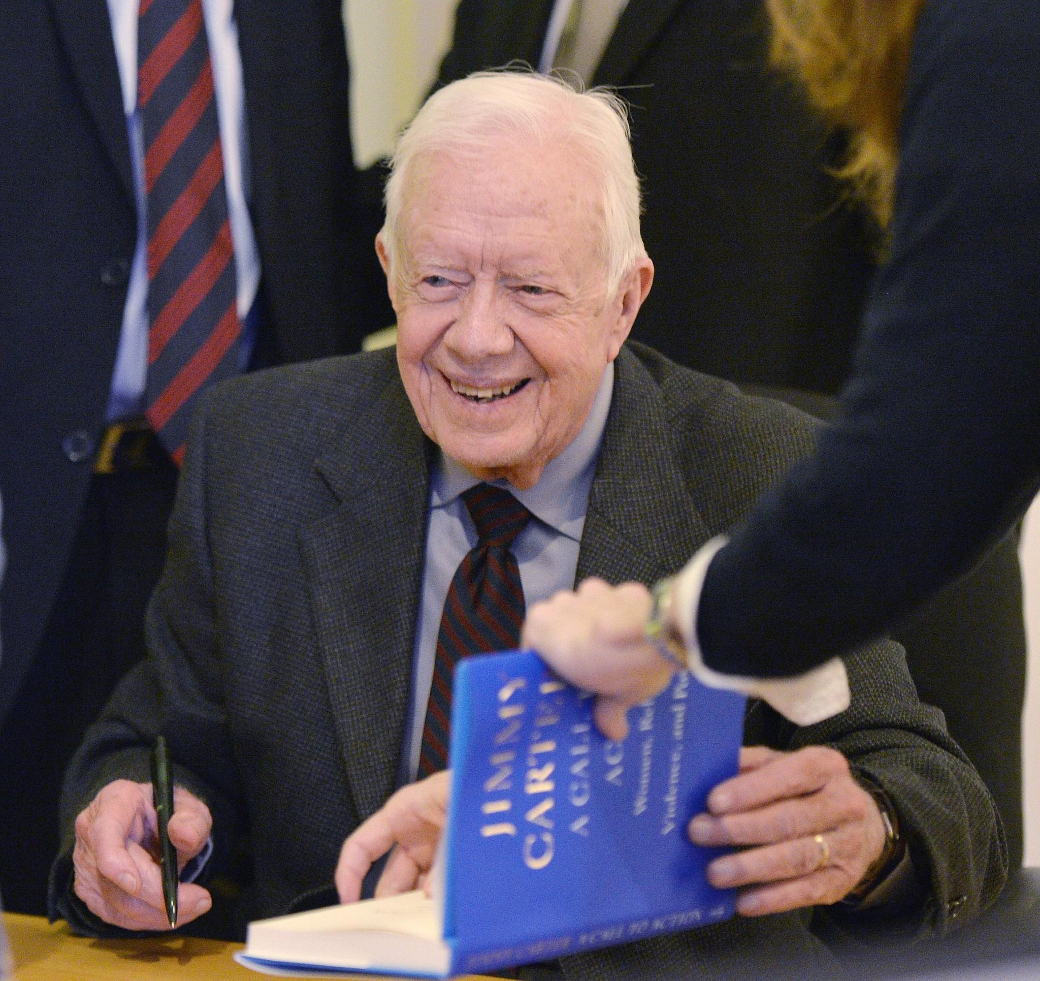 "Former President Carter signs a copy of his new book, ""A Call to Action: Women, Religion, Violence, and Power,"" at Women and Children First Bookstore in Chicago. At a stop in Portland, Ore., he signed 1,600 copies in one sitting."