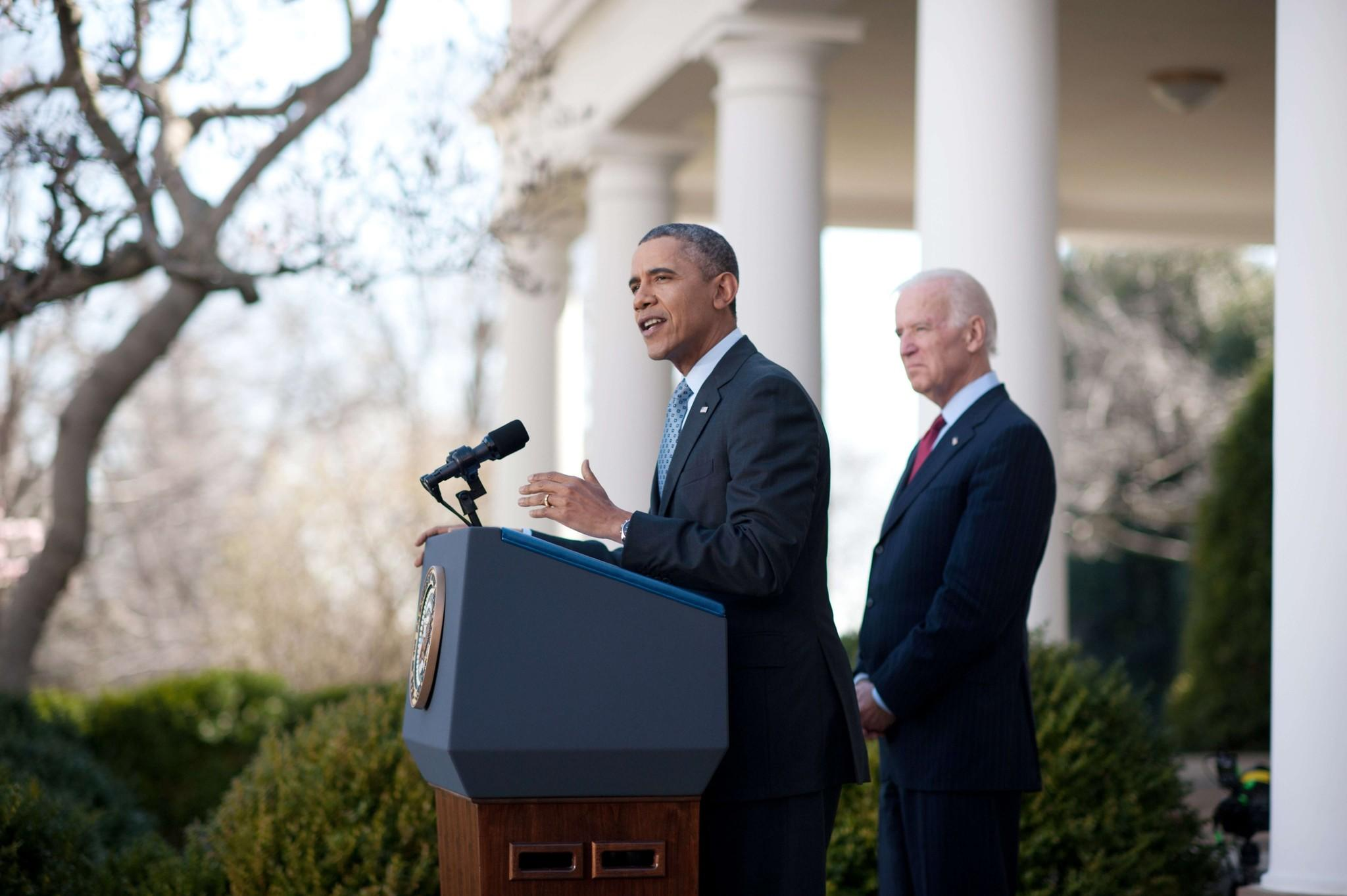 President Obama touts the Affordable Care Act, saying 7.1 million people have signed up, as Vice President Joe Biden listens in the White House Rose Garden.