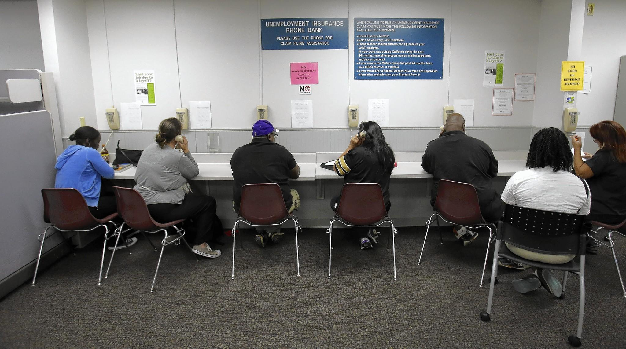 Visitors use the unemployment insurance phone bank in the California Employment Development Department office in Sacramento.
