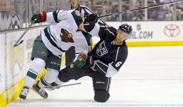 Jake Muzzin and Minnesota's Stephane Veilleux tumble to the ice during the Wild's 3-2 win Monday over the Kings.