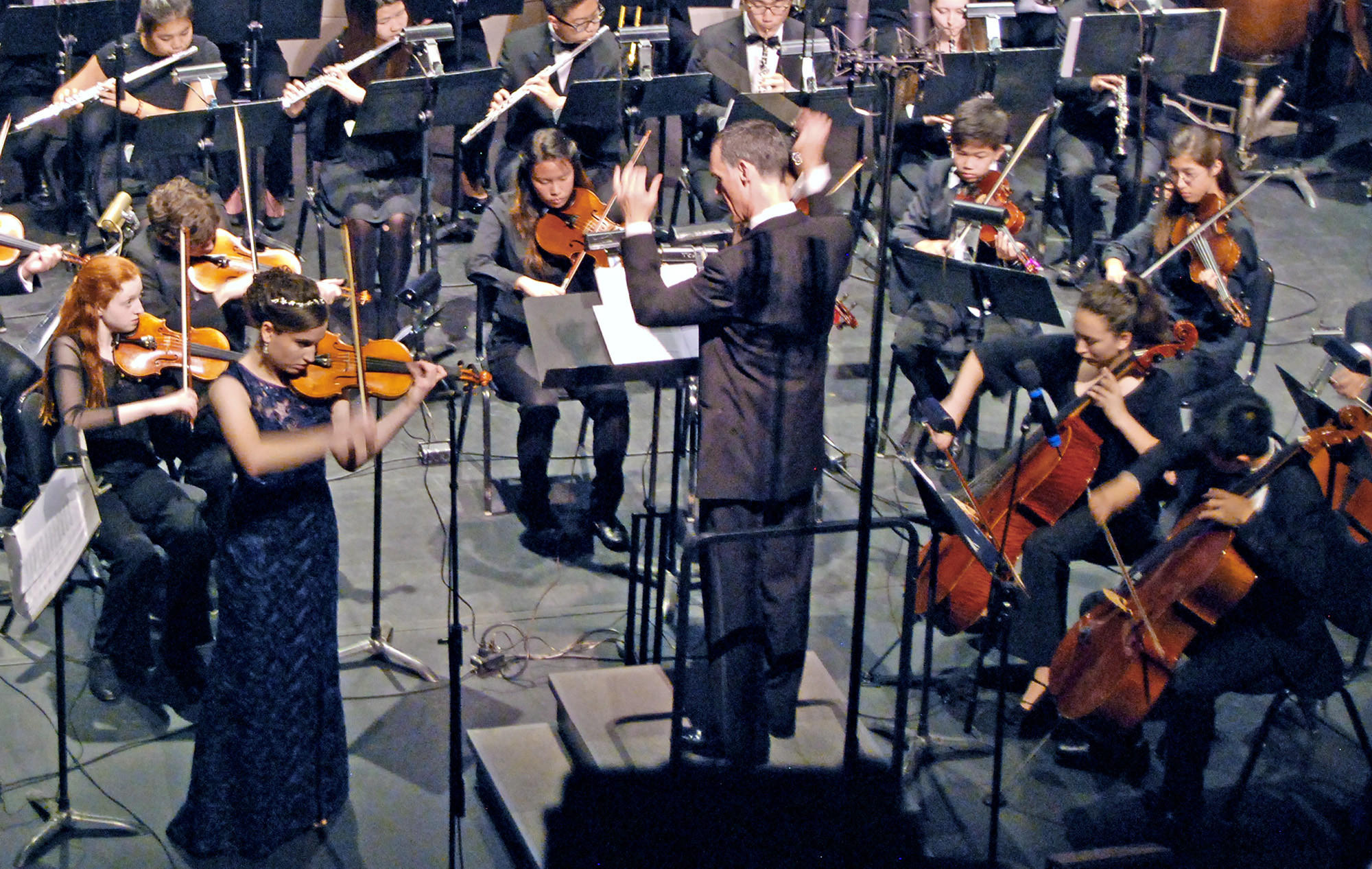 Concertmaster Sarah Worden, standing, performs Beethoven's Concerto for Violin while conductor Brad Keimach directs the Glendale Youth Orchestra at the Alex Theatre.
