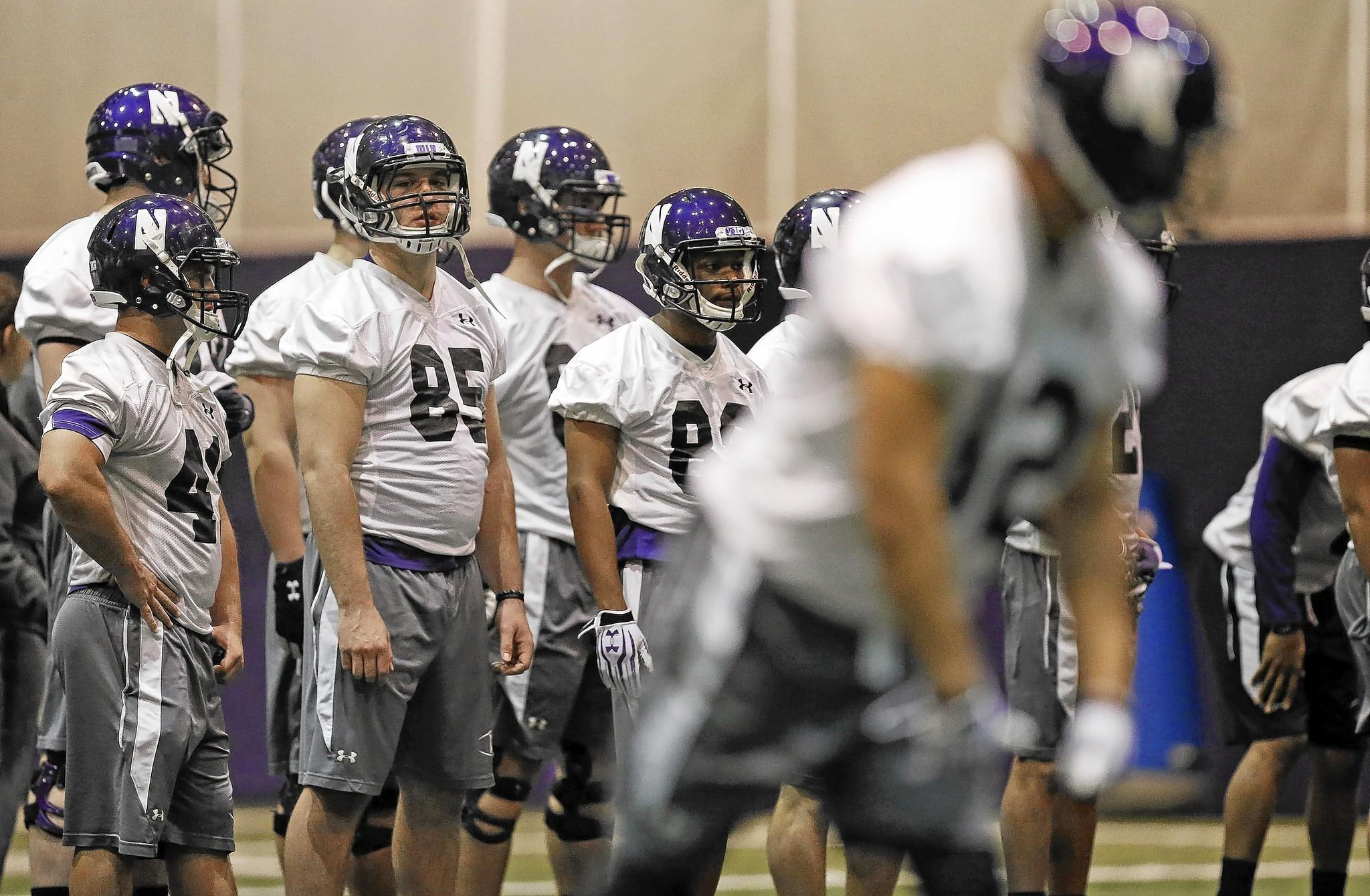 Northwestern University football players run drills Tuesday during spring practice. Last week, the National Labor Relations Board's regional director ruled that NU's football players on athletic scholarships are university employees and, as such, their petition for a union election can move forward.