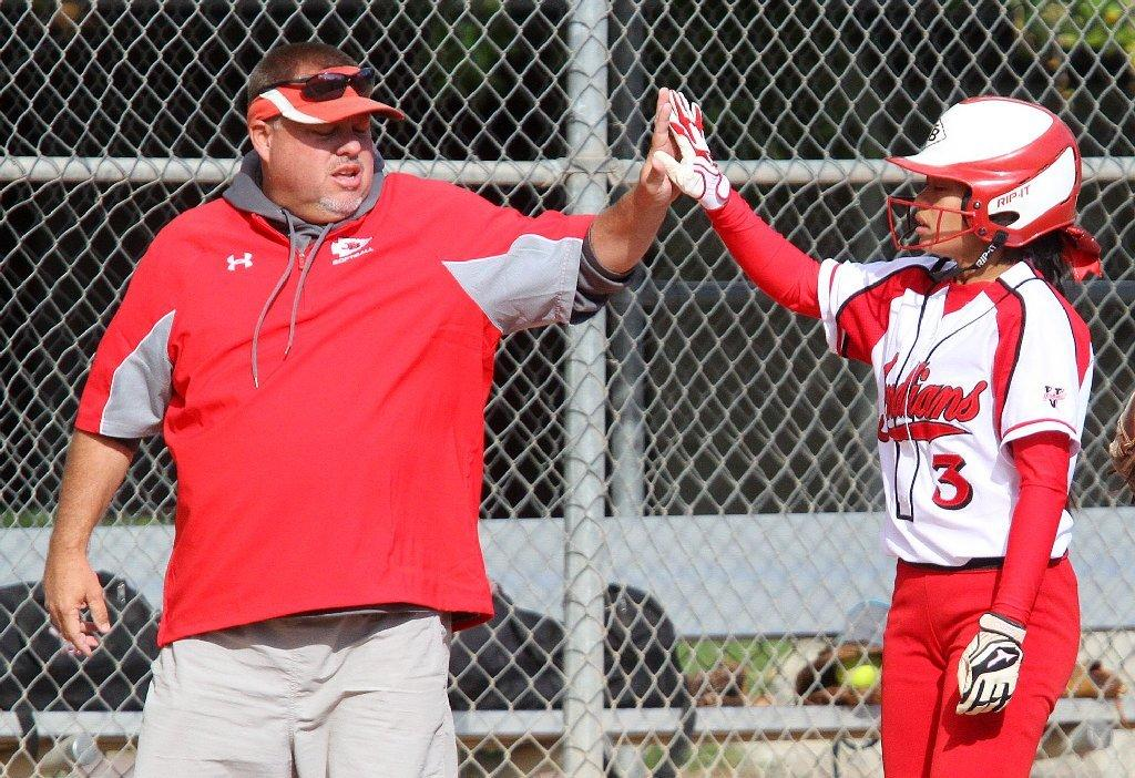 Burroughs' Coach Doug Nicol high fives Sidney Ortega, who safely reached third base against Glendale in a Pacific League softball game at Olive Park in Burbank on Tuesday. Burroughs won the game, 11-1. (Tim Berger/Staff Photographer)