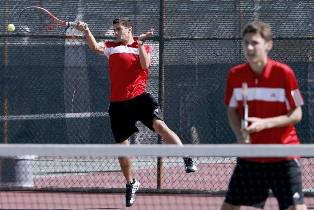 With his partner David Casaburi looking on, Glendale High School's No. 1 doubles player, Mheir Krikorian, returns the ball during a Pacific League match versus Hoover High at Glendale High on Tuesday. (Raul Roa/Staff Photographer)
