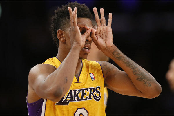 "Lakers forward Nick Young dons his ""3-point goggles"" as he celebrates a basket against the Portland Trail Blazers."