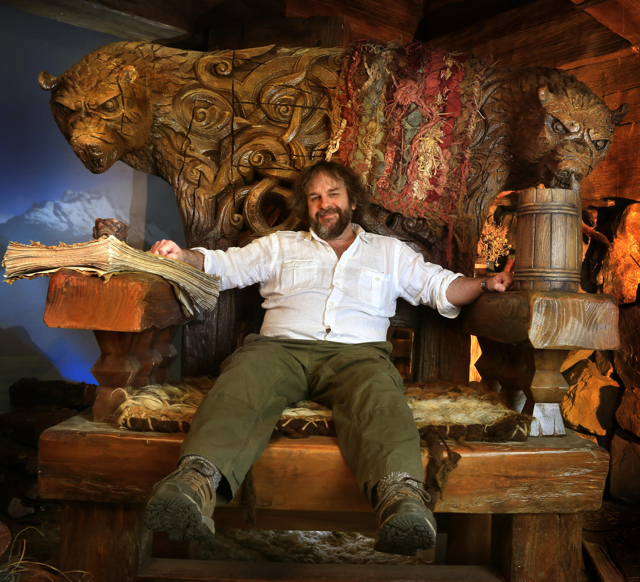 """Director Peter Jackson sits in one of the giant chairs from """"The Hobbit: The Desolation Of Smaug,"""" part of a display in Beverly Hills."""