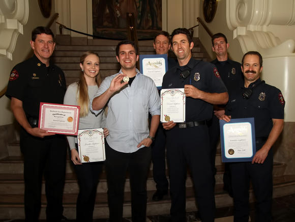 Members of the Burbank Fire Department, along with City Council members, honored Konrad Lightner and his wife, Jennifer, after they saved the life of a 3-year-old boy who fell from a third-story window.