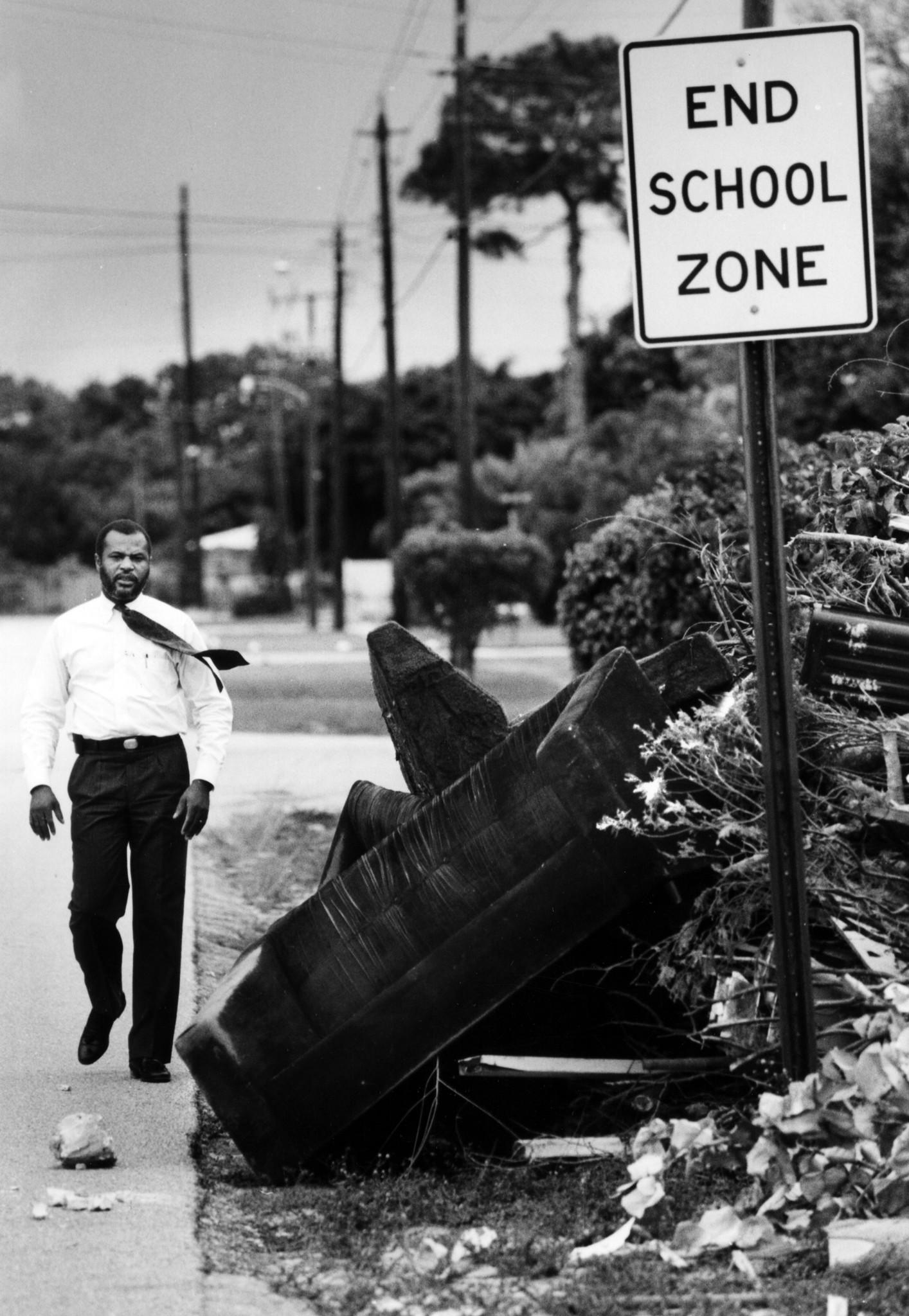 Fort Lauderdale Commissioner Carlton Moore is disgusted with the condition of many neighborhoods in the city. Moore is pictured here walking past a huge pile of trash in a neighborhood at Southwest Ninth Street and 29th Terrace. Residents said they asked for the trash to be removed, and were told it would be, yet the trash is still present. June 20.