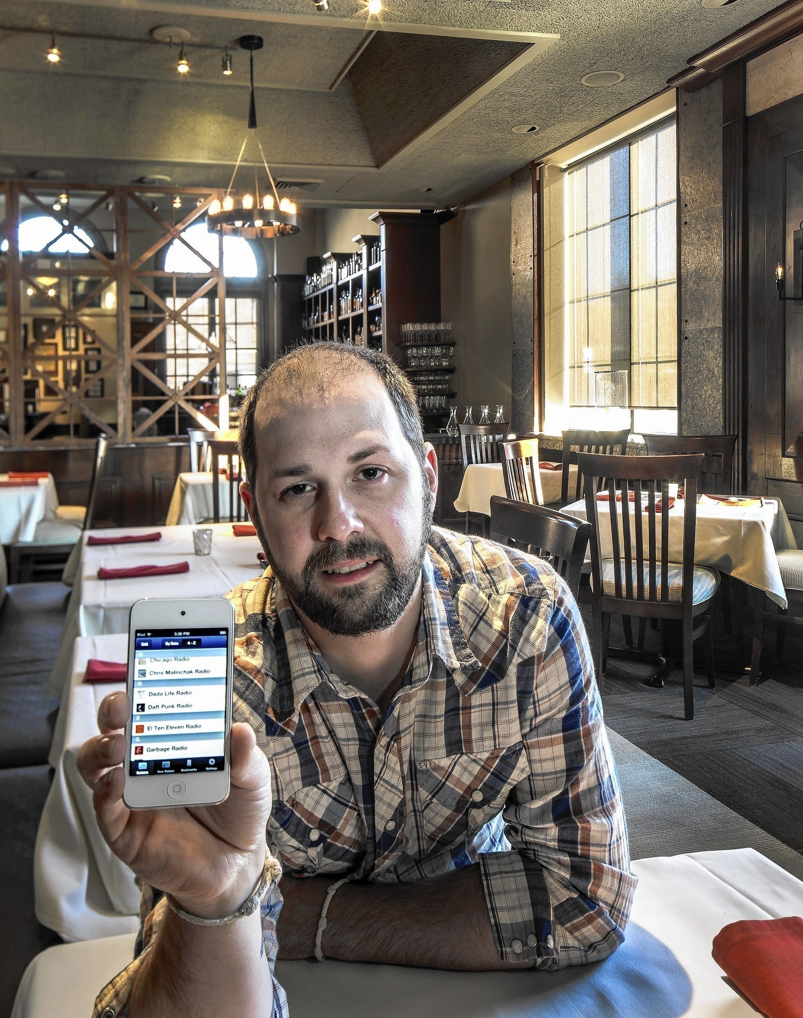 Vince Balistreri, general manager and sommelier of Niche restaurant in Geneva, IL, Balistreri is holding his iPhone featuring the playlist from Pandora that is used in the restaurant.