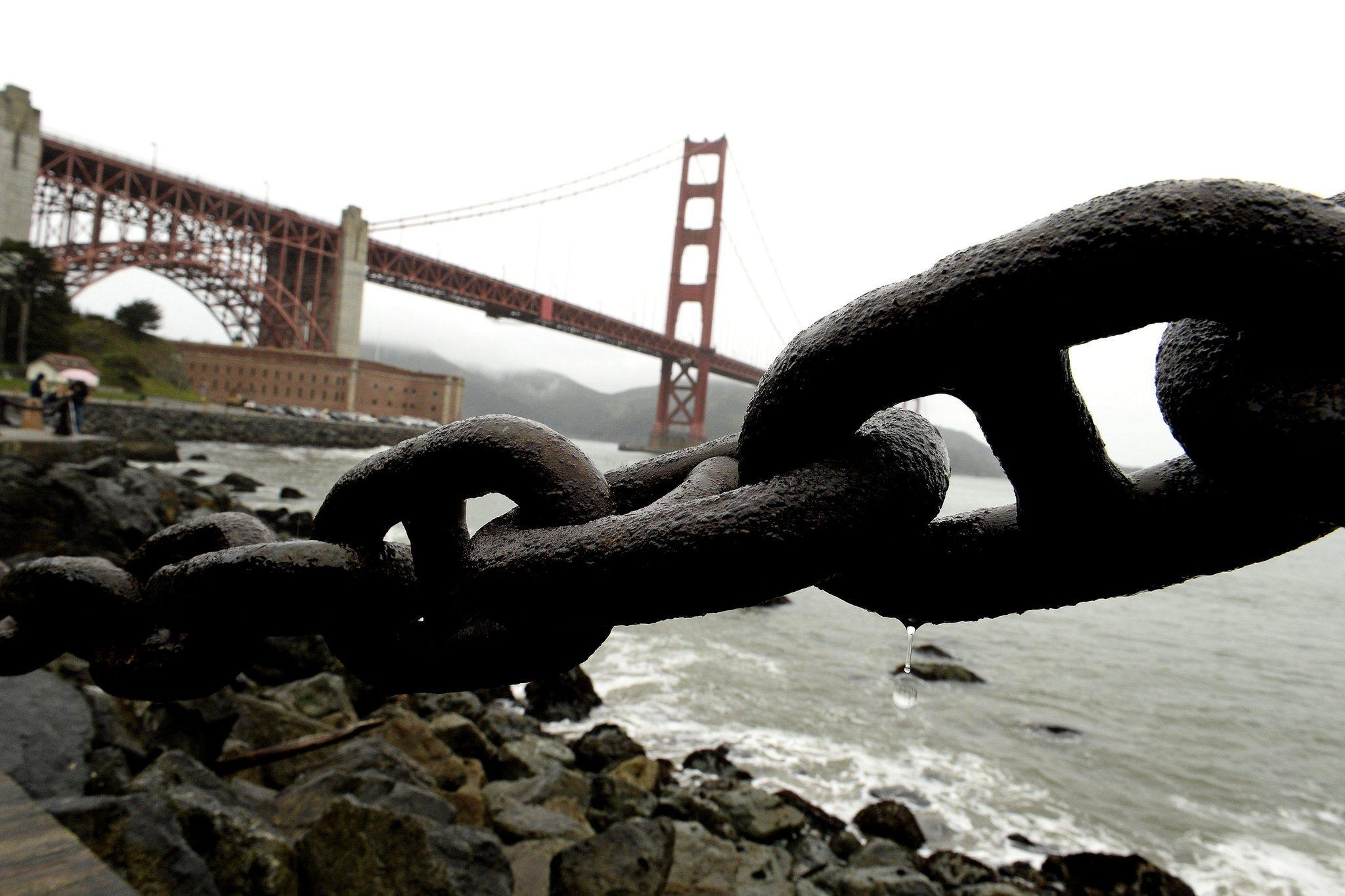 Water drips from a chained barrier along the San Francisco Bay during a storm on Monday that produced multiple lightning strikes.