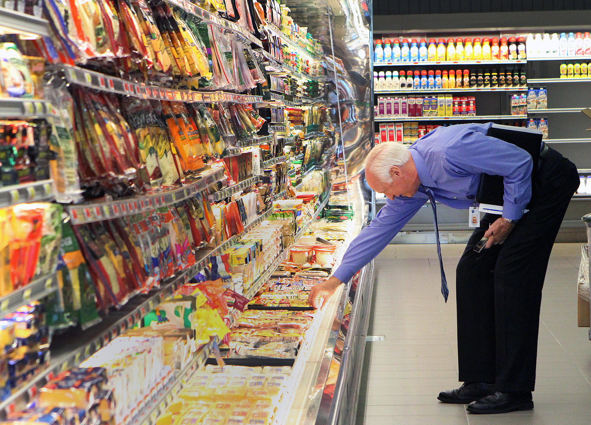 Jim Veregge, of Unified Grocers, checks shelves in a refrigerated section to make sure products his company provides are well presented and fully stocked at Gelson's in La Cañada Flintridge on Monday, March 24, 2014. The store had its grand opening on March 27 at 9:00 A.M.