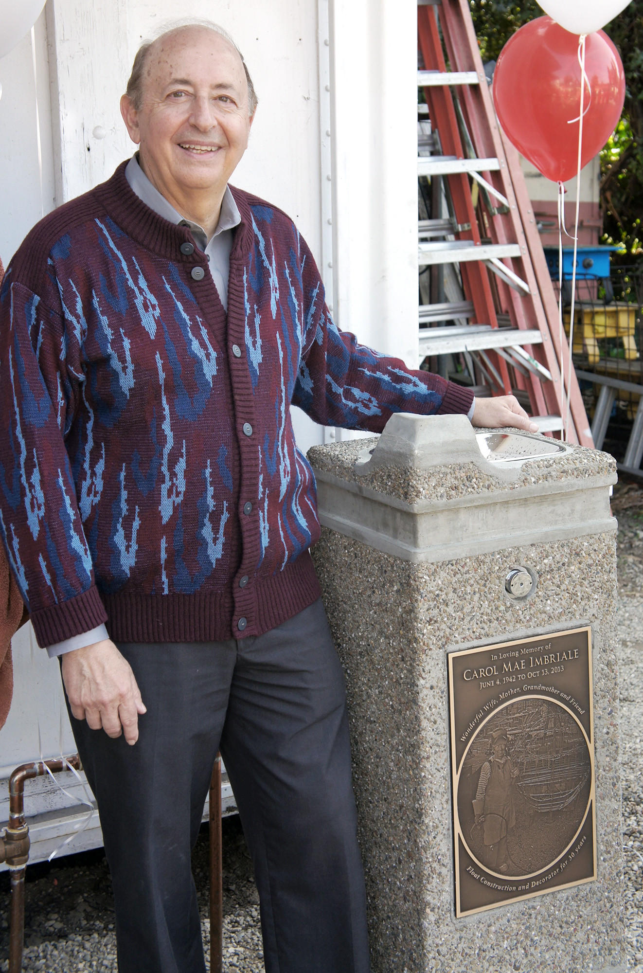 La Cañada resident Bill Imbriale stands next to a memorial drinking fountain dedicated Saturday to his wife, Carol Imbriale, by the La Cañada Flintridge Tournament of Roses. For more than 30 years, Carol Imbriale built and decorated floats and was often seen wearing welding gear, as depicted in the fountain's plaque. (Courtesy of the LCF Tournament of Roses)