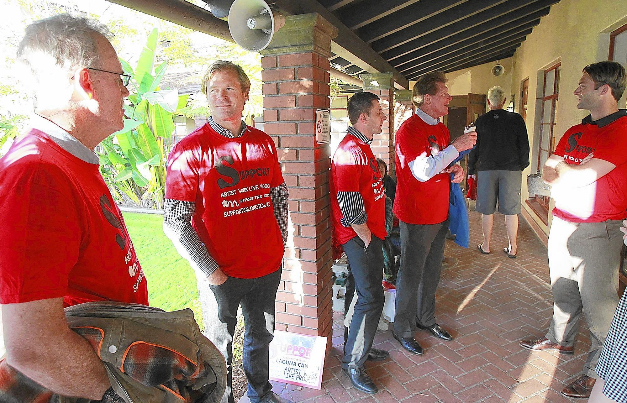 Wearing red shirts in a show of unison, supporters including project developer Chris Dornin, second from left, stand outside the Laguna Beach City Council chambers before a rule to approve a 30-unit artist live-work project in Laguna Canyon during Tuesday's City Council meeting.
