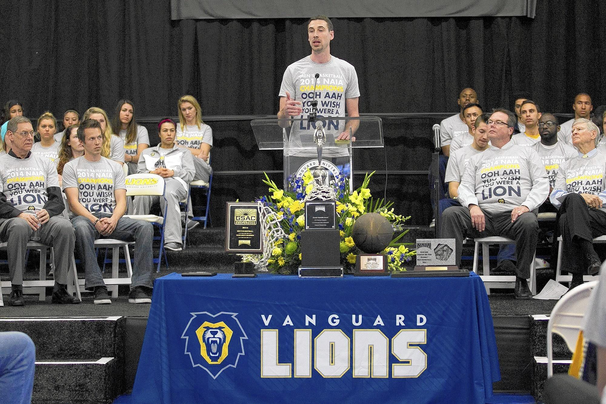 Rhett Soliday, the head coach for the Lions mens' basketball team, speaks to the crowd during a 2014 NAIA Basketball National Championship rally at Vanguard University on Wednesday.