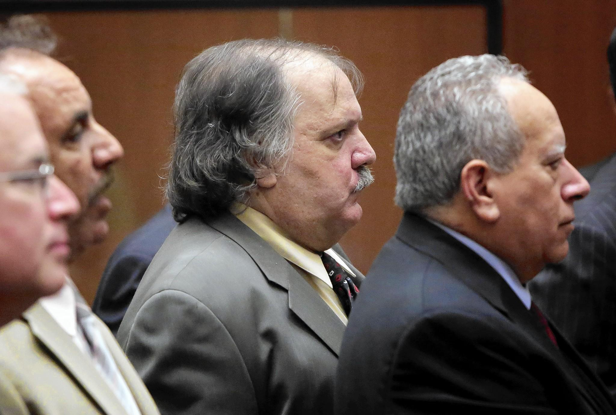 Former Bell council member Victor Bello, center, is among five ex-Bell officials who are considering a plea deal.