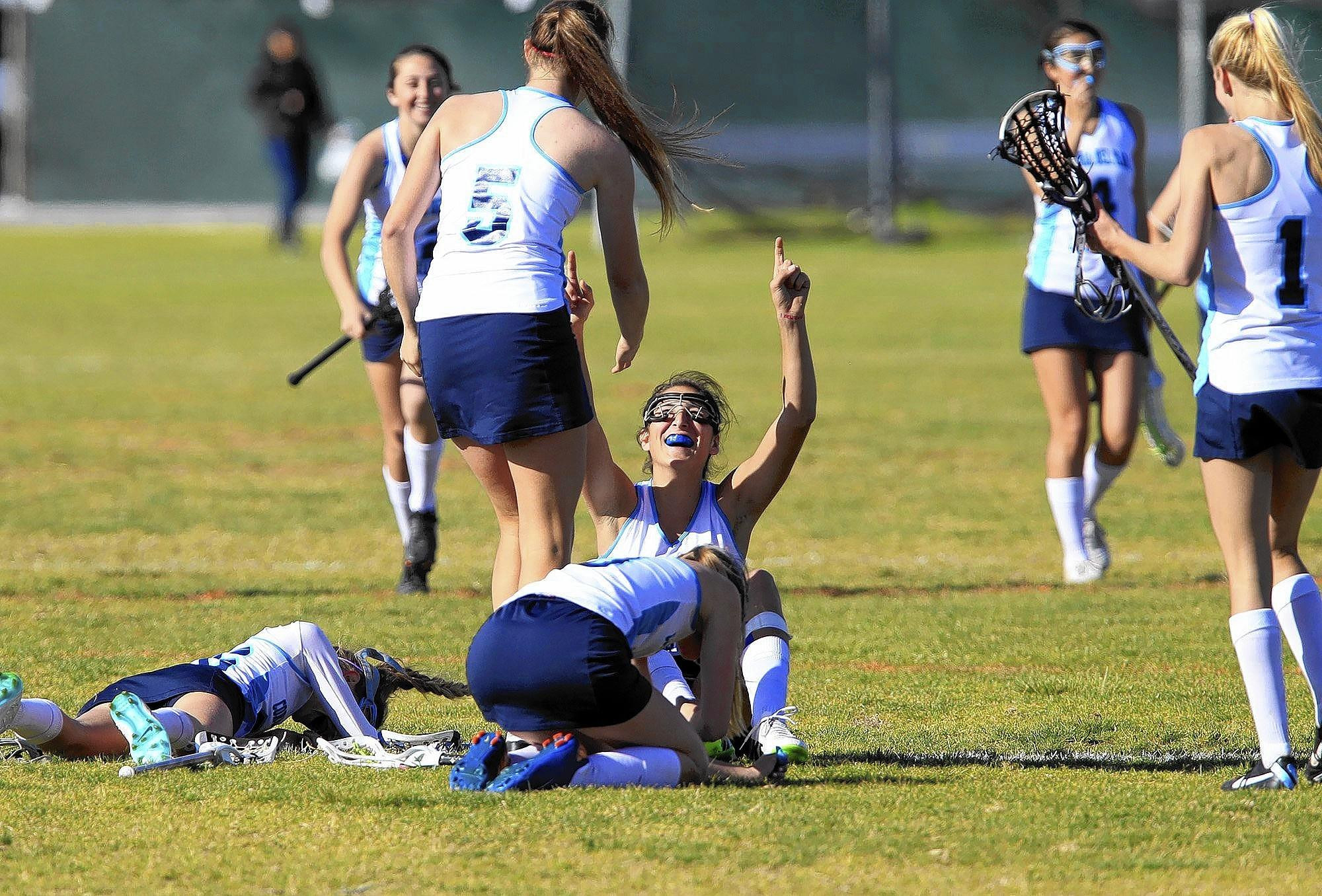 Corona del Mar High's Sabrina Smith, sitting center, cheers as she's helped up by teammate Kendall Mulvaney (5) after the Sea Kings beat Beckman, 15-11, in a Pacific Coast League game on Wednesday. Smith tripped as she ran to celebrate with teammates.