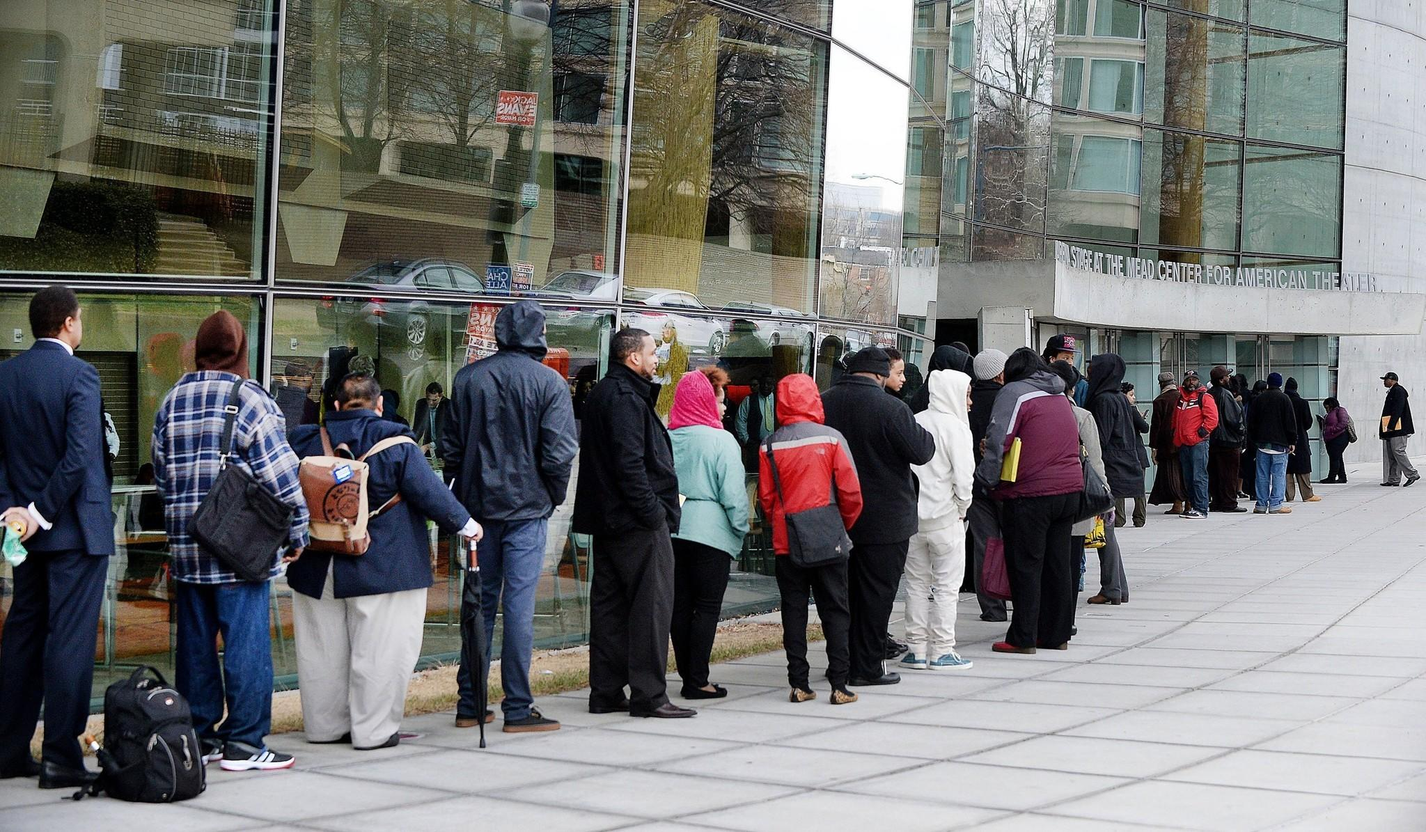 Job seekers wait in line to enter a job fair at the Arena Stage in Washington.