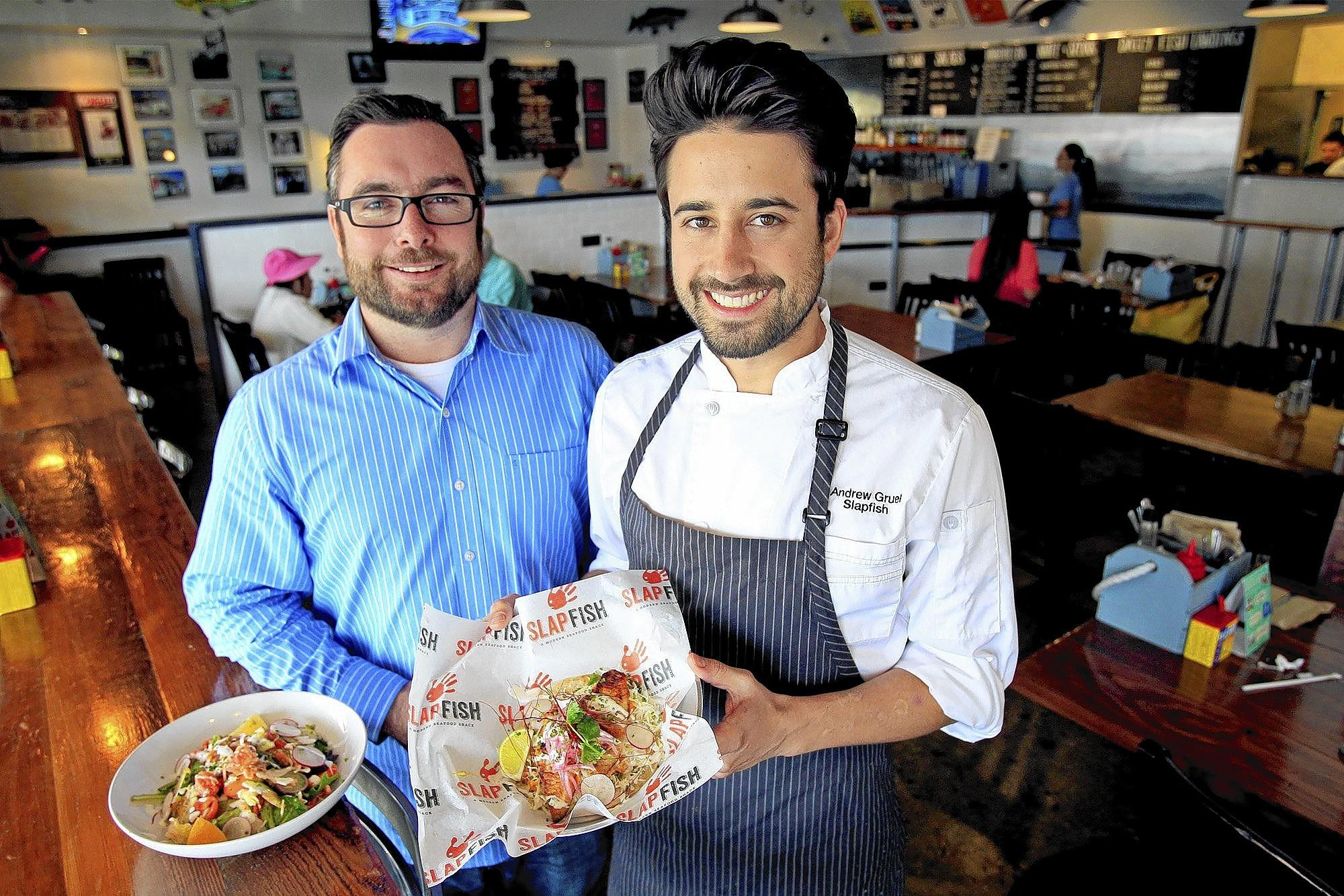 Co-founders Andrew Gruel, 33, center, and Jethro Naude at Slapfish in Huntington Beach. They're opening a second location in Laguna Beach.