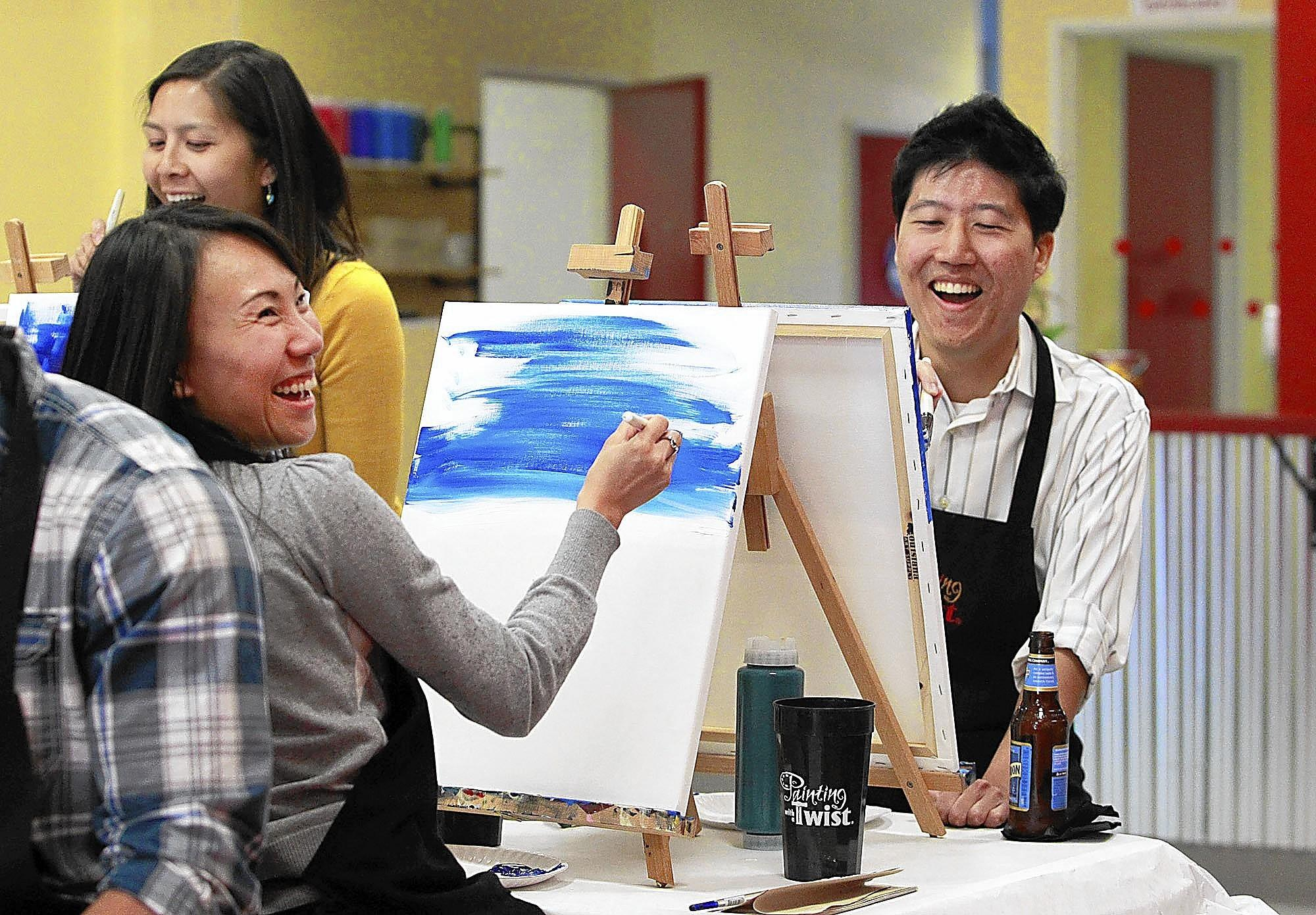 Co-workers Yan Song, left, and Stephan Choi laugh as they start a painting with their private party group in the Painting with a Twist concept in Huntington Beach.