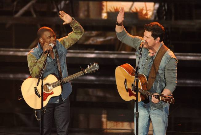 "C.J. Harris, left, and Dexter Roberts high five after performing ""Alright"" on ""American Idol."""