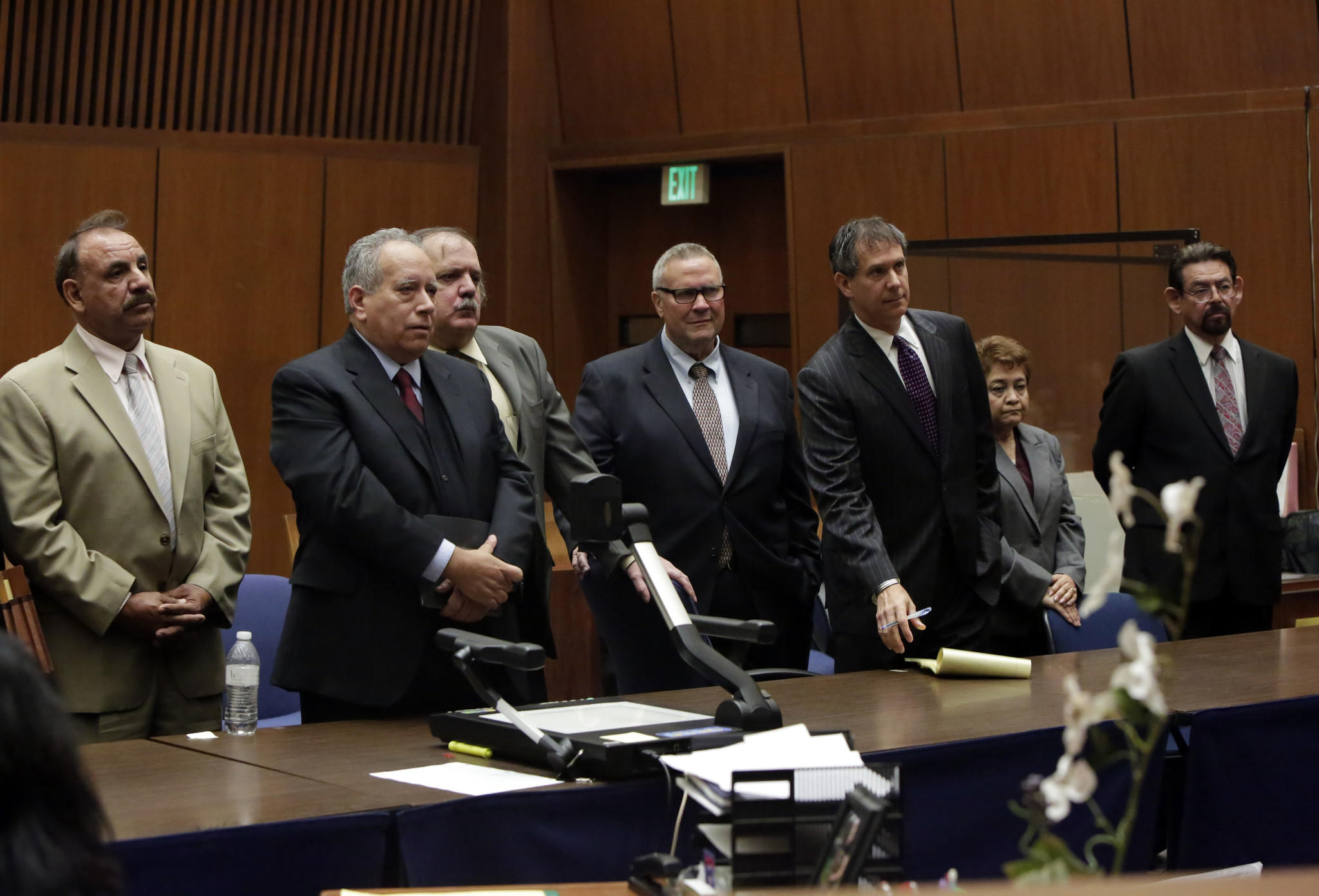 Oscar Hernandez, left, stands with Victor Bello and George Cole, third and fourth from left, Teresa Jacobo, second from right, and George Mirabal, right. The other men pictured, second from left and third from right, are defense lawyers.