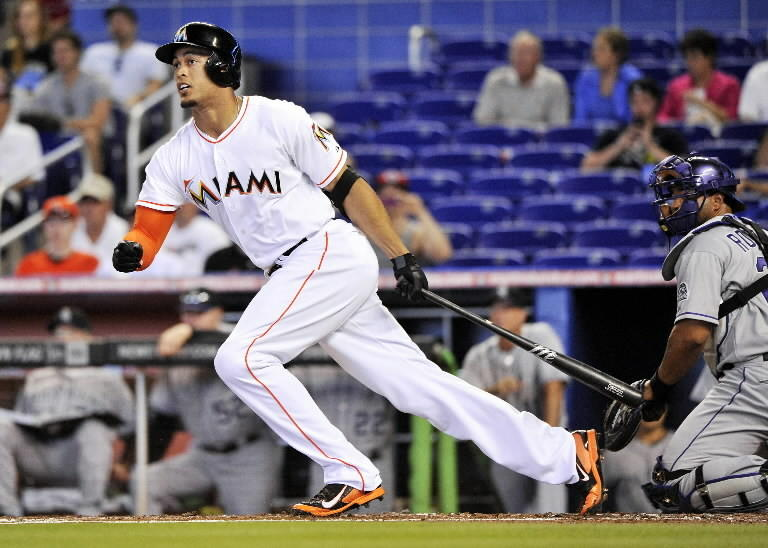 Miami Marlins right fielder Giancarlo Stanton (27) connects for a double during the first inning against the Colorado Rockies at Marlins Ballpark.