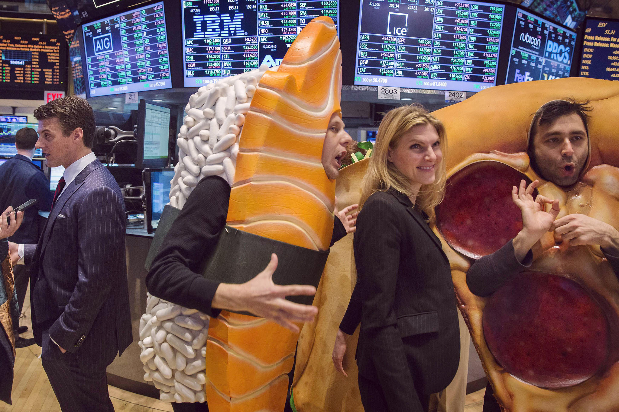 GrubHub CEO Matt Maloney, left, is interviewed on the floor of the New York Stock Exchange as people in food costumes mill about the floor.