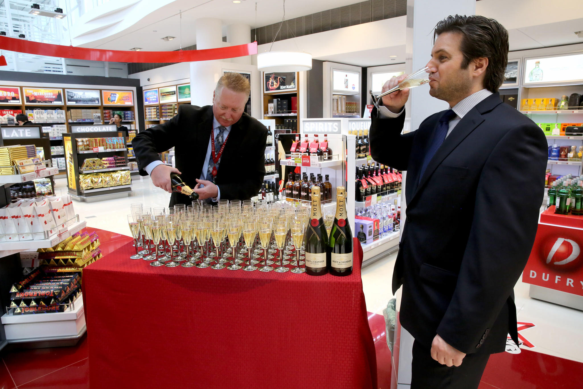 Kenneth Williamson, left, of Dufry serves up the champagne as Christopher Cassettari takes a sip at the new International Terminal 5 (T5) at Chicago O'Hare International Airport.