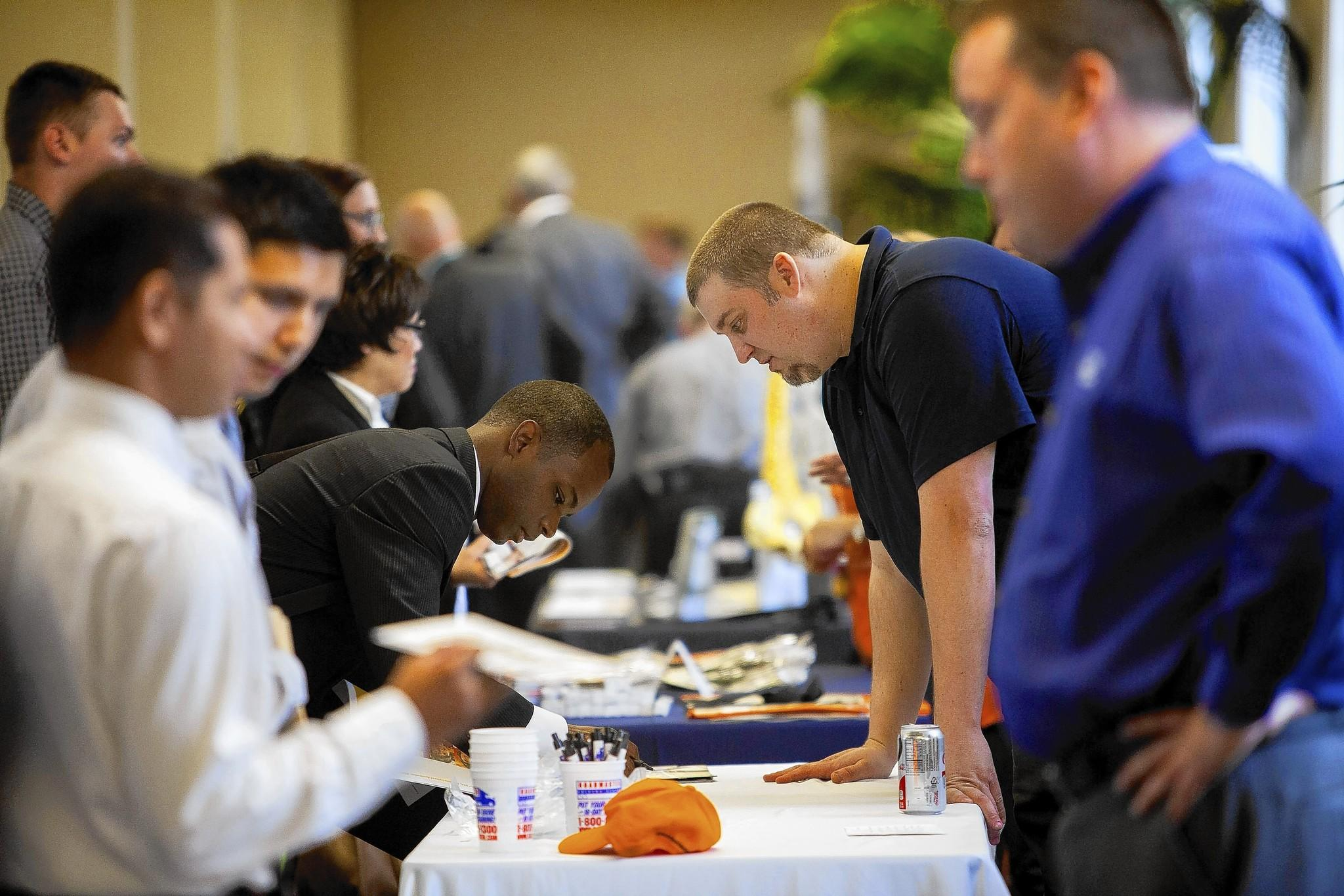 All of the jobs added in March came in the private sector, lifting total non-government payrolls to a new peak. Above, job seekers speak with representatives at a military veteran job fair in San Diego.