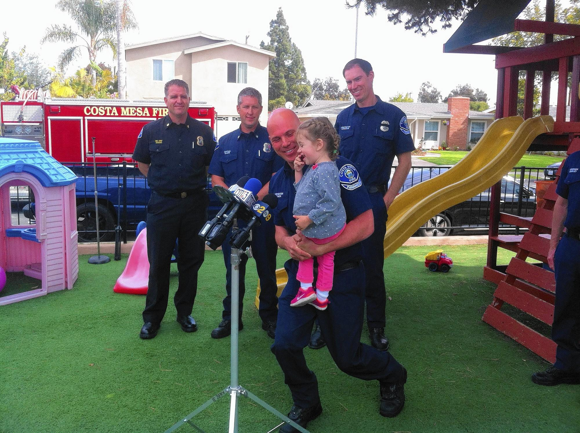 Costa Mesa paramedic Giovanni La Placa holds 2-year-old Emma Scott up to the microphones from a few local TV stations so she can thank the firefighters and day care workers who saved her from choking.