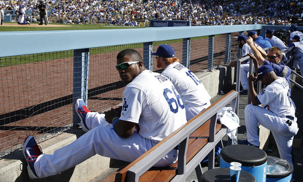 Dodgers outfielder Yasiel Puig watches Friday's home opener against the San Francisco Giants from the dugout after he was benched by Manager Don Mattingly for arriving late to the ballpark.
