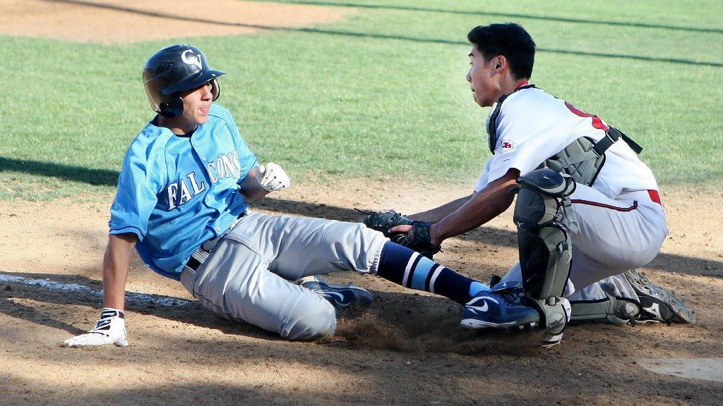 Burroughs High's Roy Hirota, right, tags out Crescenta Valley's Adrian Damla at home plate in a Pacific League baseball game at Burroughs High on Friday. Crescenta Valley won the game 4-1. (Tim Berger/Staff Photographer)