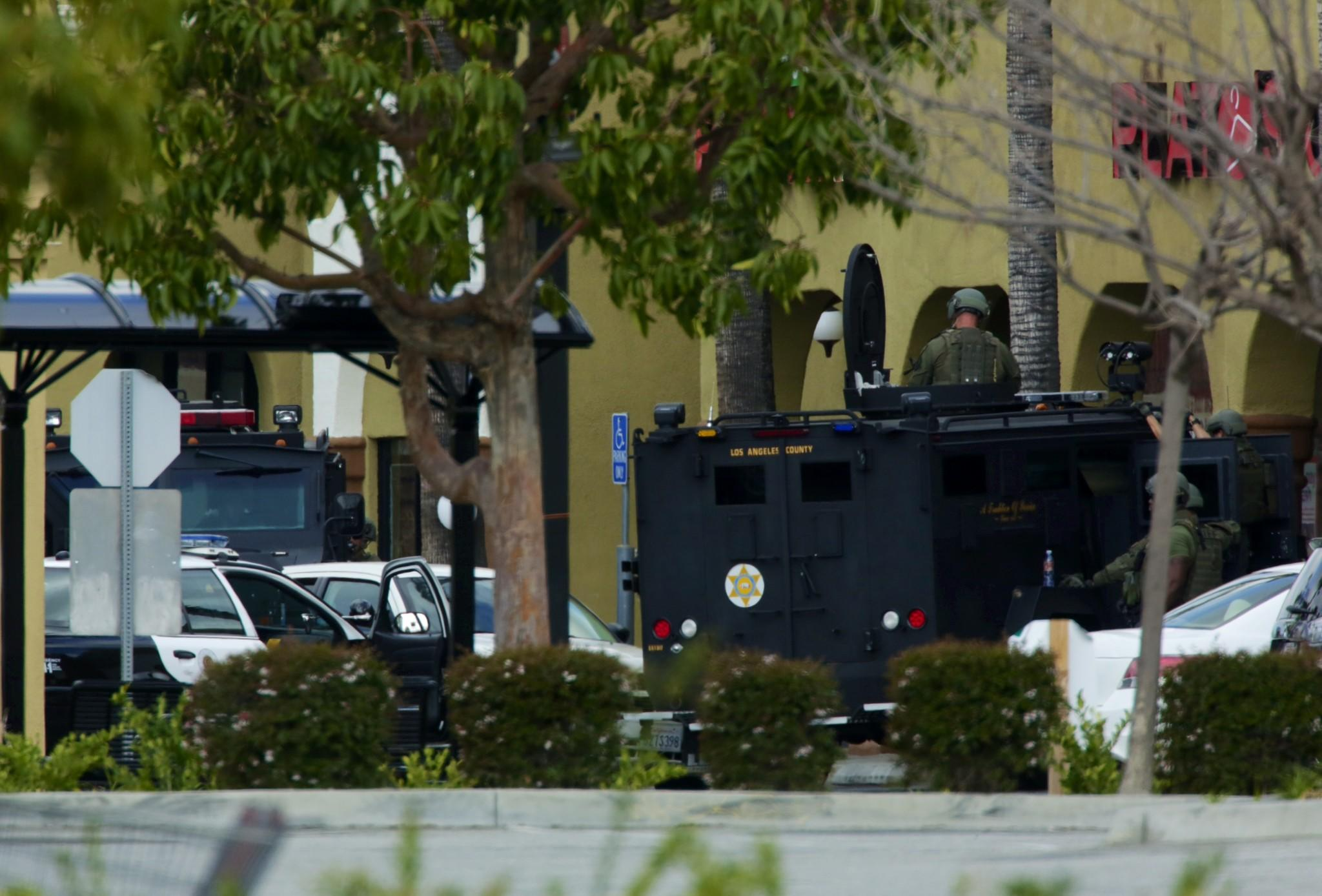 Law enforcement vehicles surround a suspected shooter inside a white Dodge Magnum in the parking lot of a shopping plaza on Carson Street in Hawaiian Gardens.