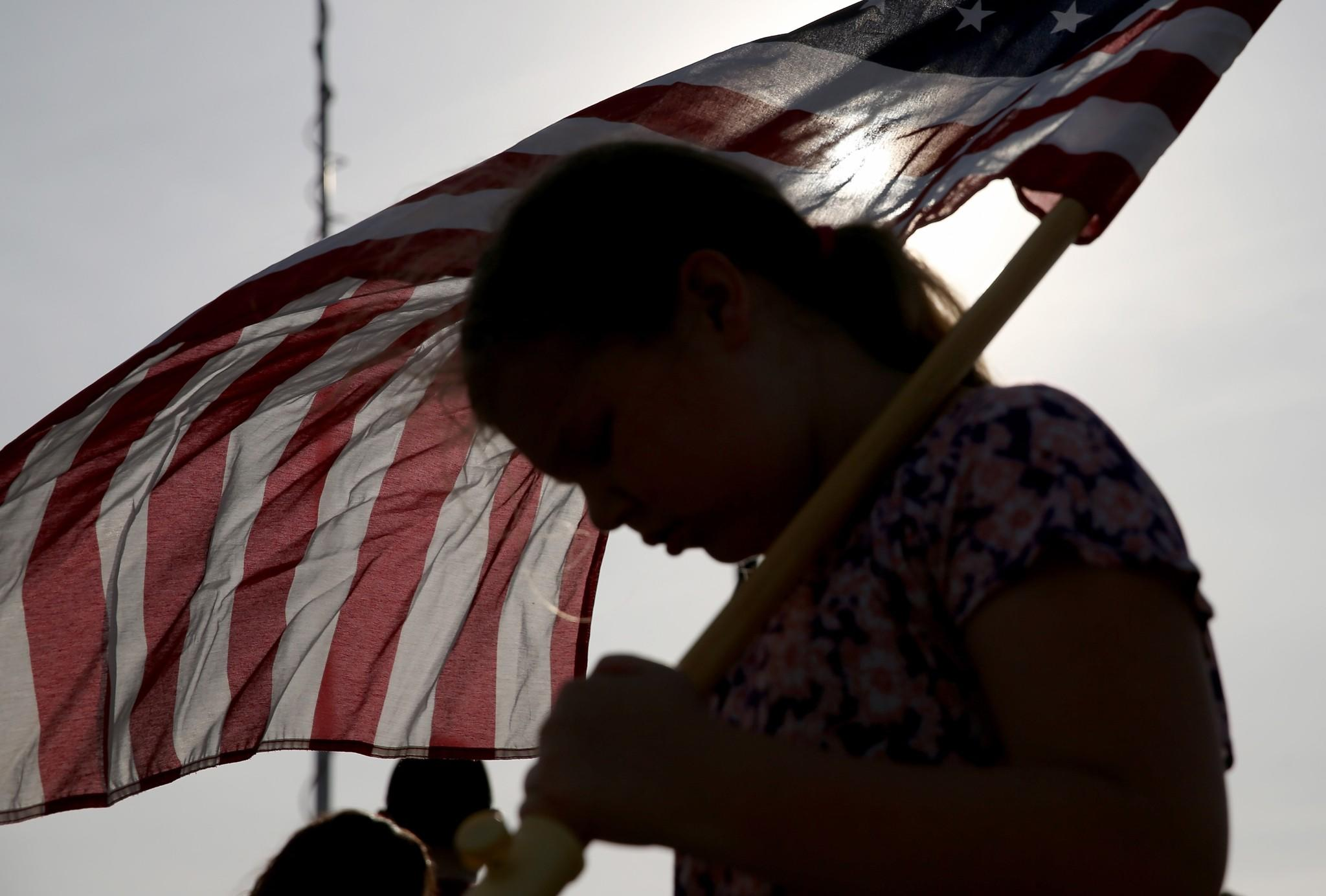 Jenna Ryan, 11, holds a flag as she participated Friday in a flag walk in memory of those killed and injured on the Ft. Hood Army post this week.