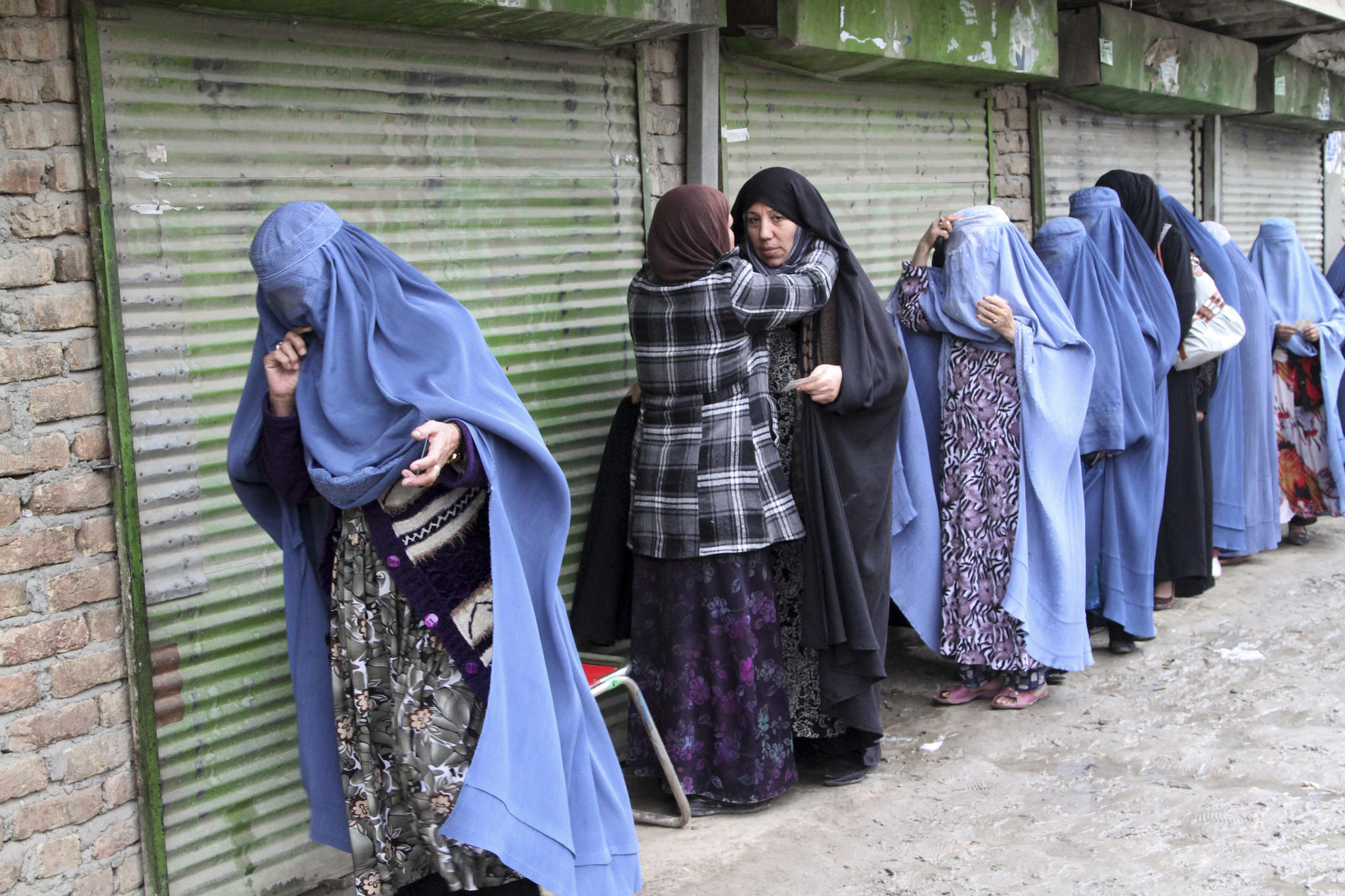 Female voters are searched by a poll worker before they enter a polling station in Kabul on Saturday.