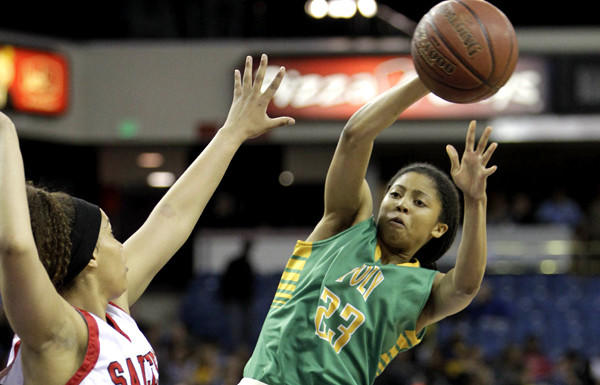 Long Beach Poly guard Arica Carter passes around Salesian forward Alana Horton during the first half of the Open Division state championship game.