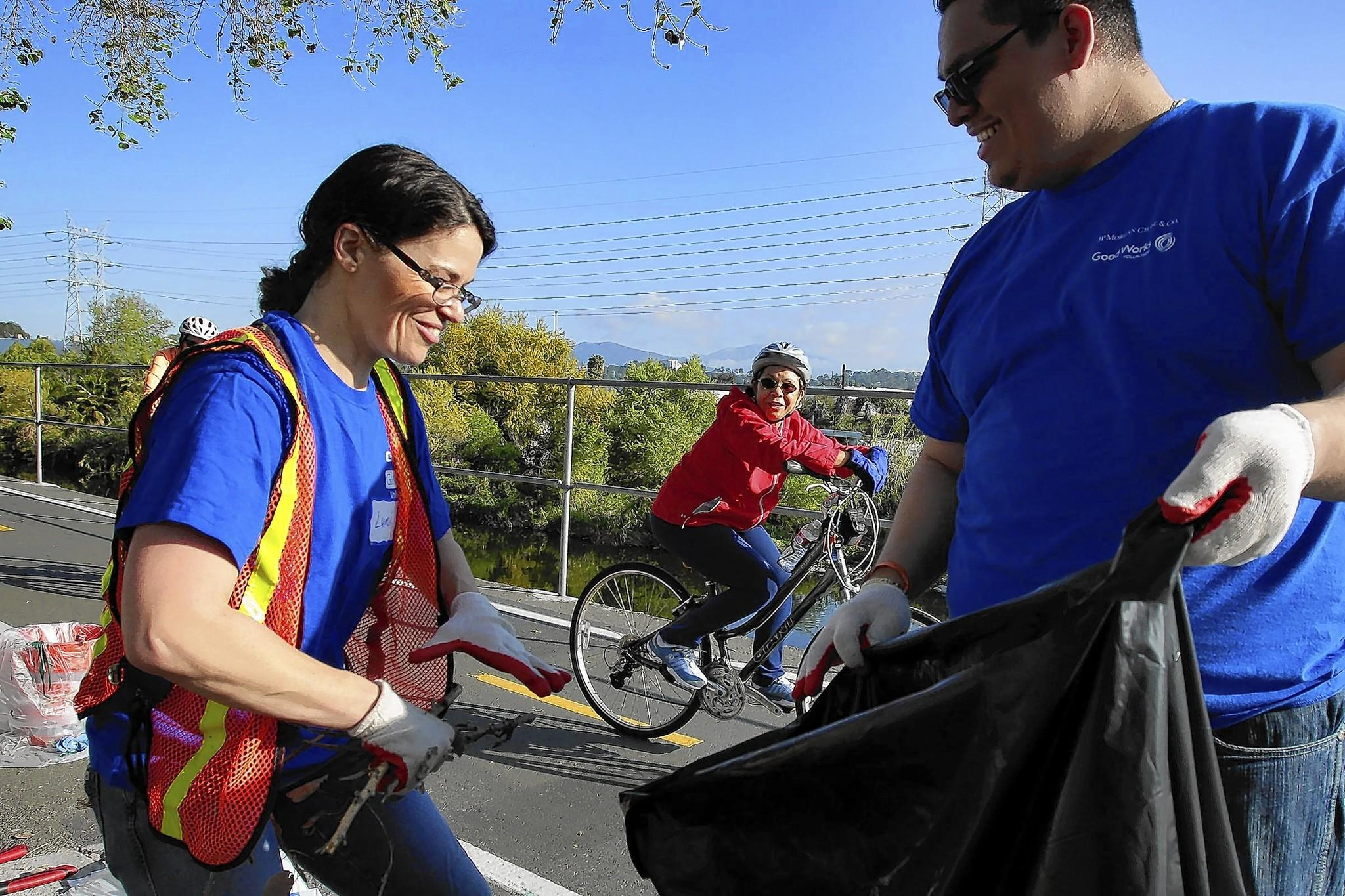 A bicyclist encourages volunteers Lumi Powell and Tomas Marquez, who were removing weeds and dead tree branches alongside the L.A. River as part of an ongoing effort by city officials and the community to restore the waterway.