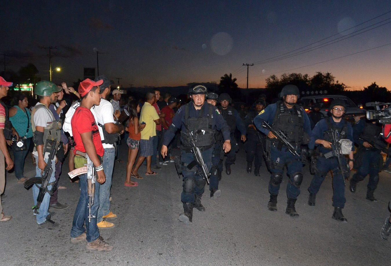 The detention of the interior minister of Mexico's western state of Michoacan appears to bolster accusations by vigilante groups that state officials have colluded with narcotics traffickers. Here, federal police guard the streets last month as members of a vigilante 'self-defense' group observe them in the village of La Ruana, Mexico.