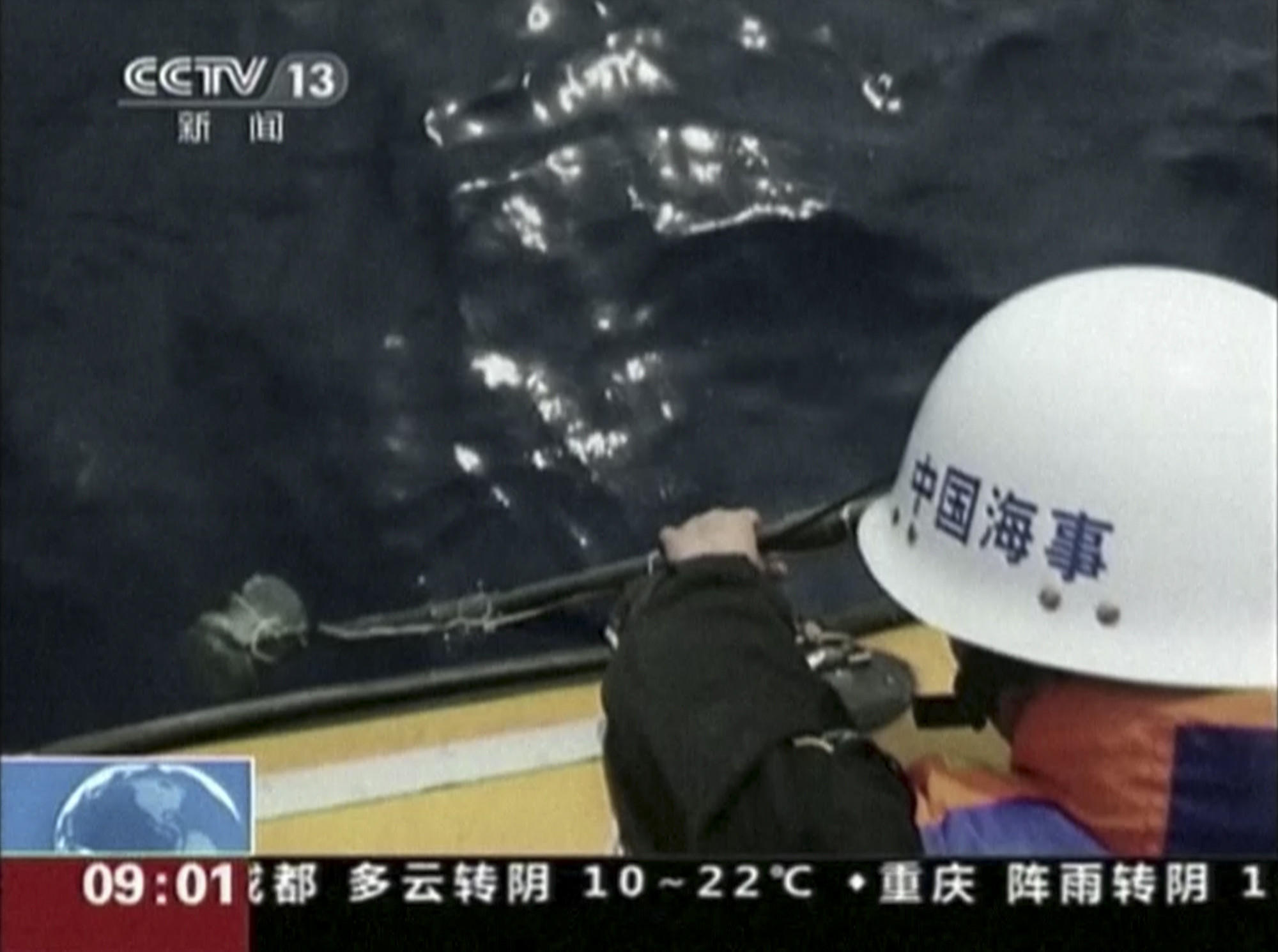 In this image taken from video, a member of a Chinese search team uses an instrument to detect electronic pulses Saturday while searching for the missing Malaysia Airlines Flight 370 on board the patrol vessel Haixun 01 in the south Indian Ocean.