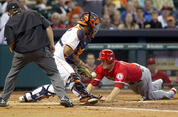 Angels third baseman David Freese dives toward home plate around Astros catcher Carlos Corporan during a play in the sixth inning Saturday night.