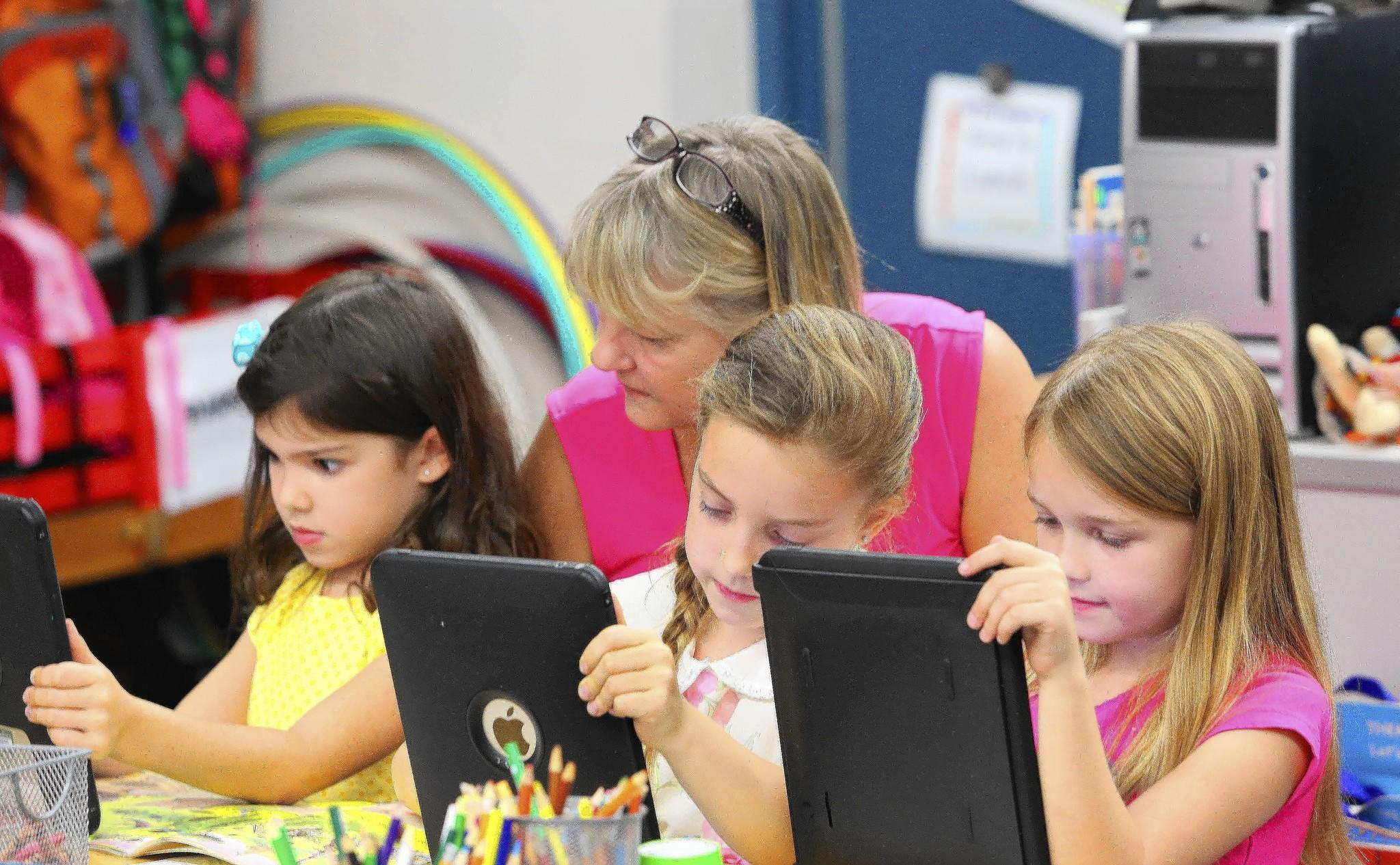 Teacher Lynn Barrett works with Addy Frohman, Abigail Dunn and Emma Mikell at Seminole Springs Elementary in rural Eustis. Barrett teaches a combined class of kindergarten through second-graders at the rural Eustis school and is likely the only teacher in Lake County portfolios to gauge their learning.