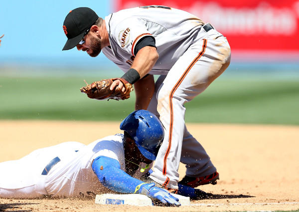 Dodgers right fielder Yasiel Puig is tagged out by Giants second baseman Brandon Hicks after getting caught in a rundown on Friday afternon.