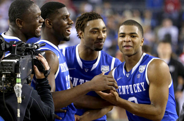 Kentucky guard Aaron Harrison, right, is congratulated by teammates (from left) Julius Randle, Alex Poythress and James Young after making the game-winning shot against Wisconsin on Saturday night.