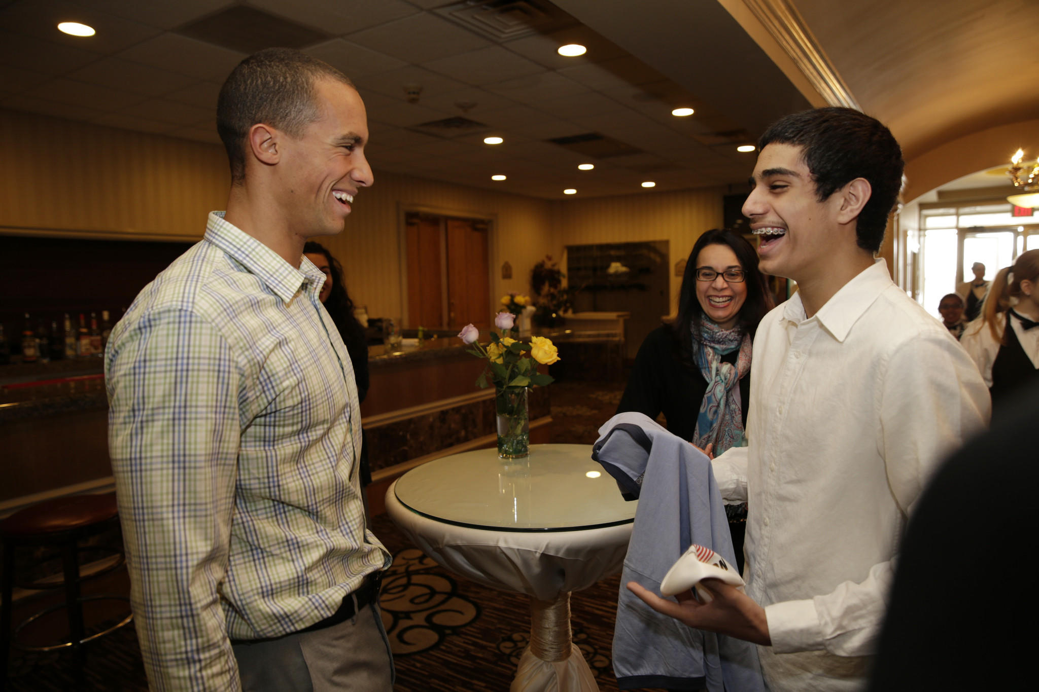 Omid Babakhani, 14, right, of Crystal Lake, is all smiles after receiving an autographed swim cap and t-shirt from BJ Johnson, left,, a member of the US National Swim Team, before the start of a swim banquet on Sunday.