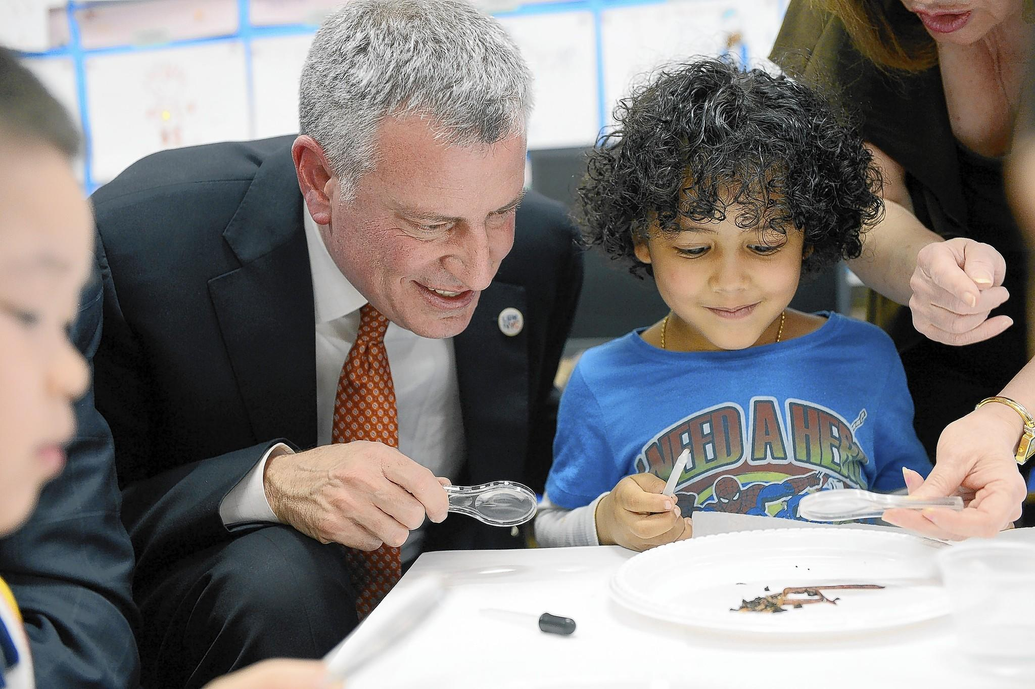 New York City Mayor Bill de Blasio works with student Justin De La Cruz on a science project at a pre-K class at P.S.1 in Manhattan. De Blasio has been fighting to rein in charter schools.